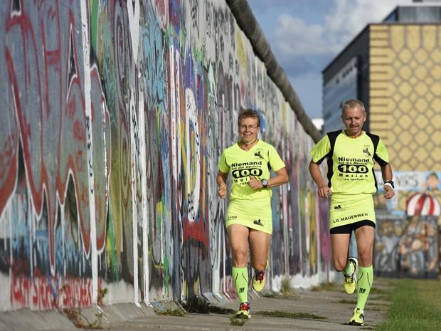 Martina Schliep e Gaston Pruefer correm ao lado do antigo Muro de Berlim durante treinamento para a maratona '100 Meilen Berlin 2014'. O evento, em 16 de agosto, homenageia aqueles que morreram ao tentar atravessar para chegar à Alemanha Ocidental (Foto: AFP Photo/Tobias Schwarz)