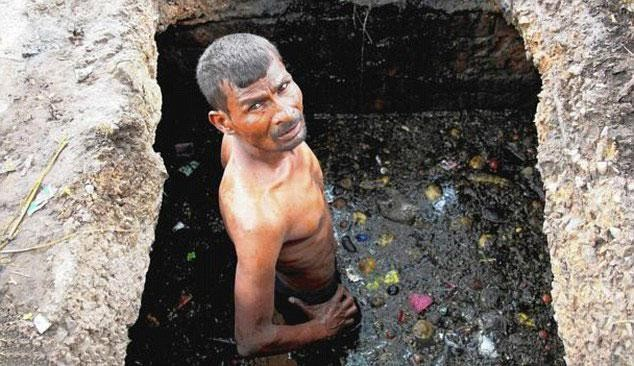 Sem qualquer proteção, o trabalho dele é desobstruir a rede de esgoto na Índia