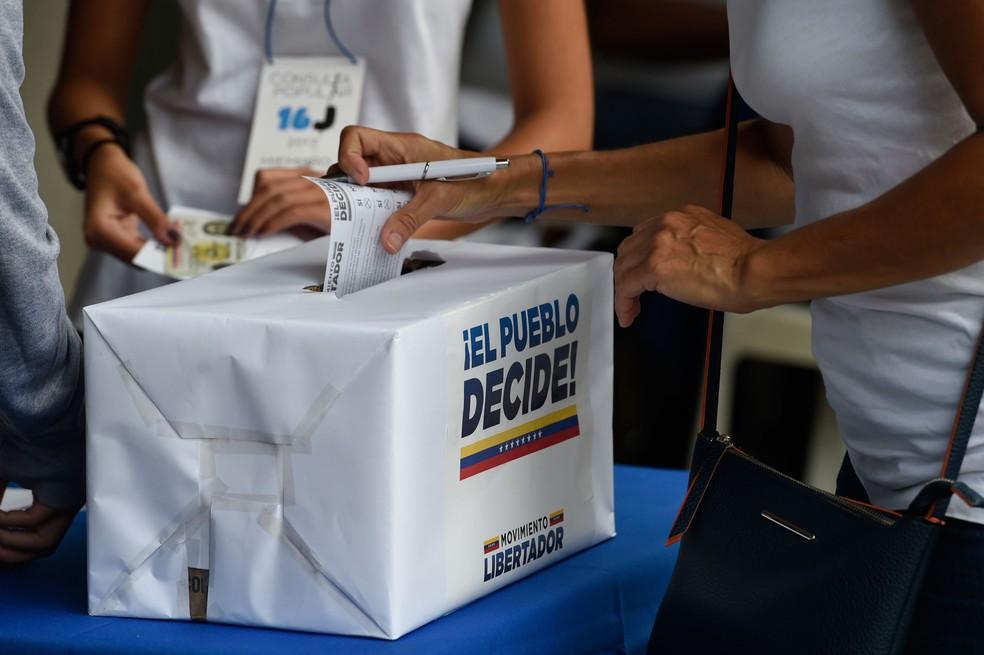 Mulher vota em plebiscito convocado pela oposição contra o presidente da Venezuela, Nicolás Maduro, neste domingo (16)  (Foto: Juan Barreto / AFP )