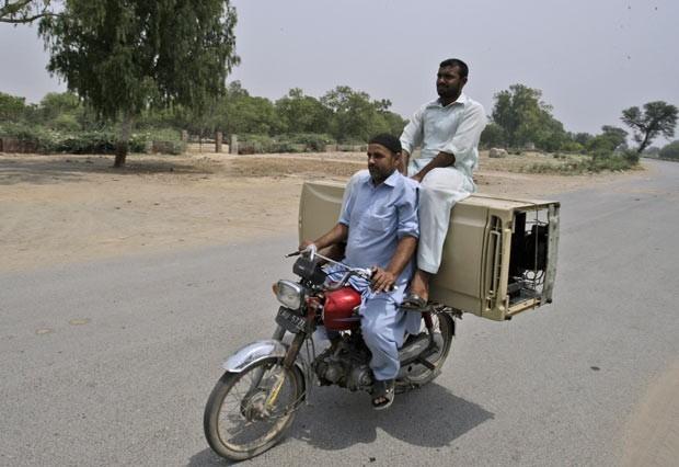 Em maio de 2012, um motociclista foi flagrado levando uma geladeira, além de um passageiro sentado sobre o eletrodoméstico, em sua moto em uma estrada em Lahore, no Paquistão (Foto: K.M. Chaudary/AP)