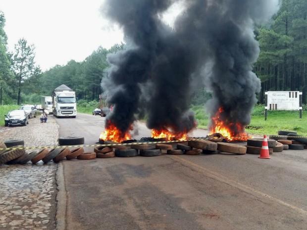 Funcionários da Araupel atearam fogo em pneus e bloquearam o trânsito na PR-473, em Quedas do Iguaçu (PR), na manhã desta segunda (26) (Foto: Araupel / Divulgação)