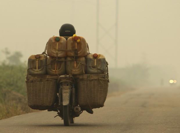 Vendedor foi visto transportando galões de óleo diesel em meio à cortina de poluição na Indonésia (Foto: Beawiharta/Reuters)