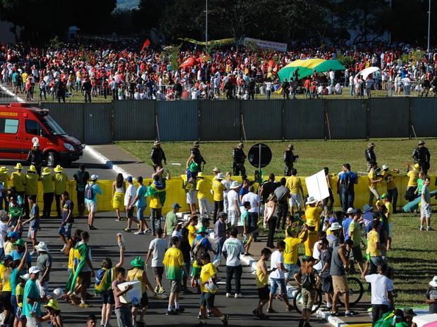 Manifestantes a favor e contra o impeachment são vistos separados por um muro na Esplanada dos Ministérios, em Brasília (Foto: Andressa Anholete/AFP)