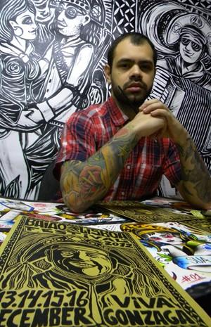 Leandro Larangeiras apresenta, em Portugal, série de desenhos inspirada na cultura nordestina. Ao fundo dois dos estandartes que serão expostos (Foto: Arquivo pessoal)