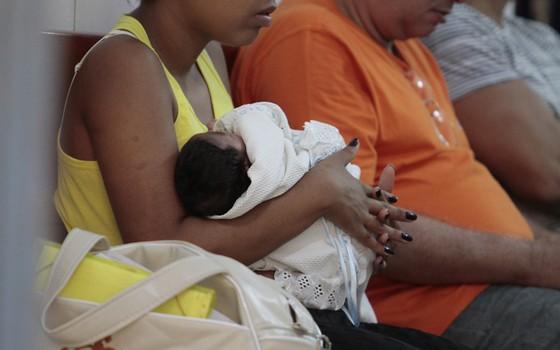 Mãe segura seu bebê, enquanto  espera por consulta sobre o caso de microcefalia  (Foto: EDMAR MELO/JC IMAGEM/ESTADÃO CONTEÚDO)