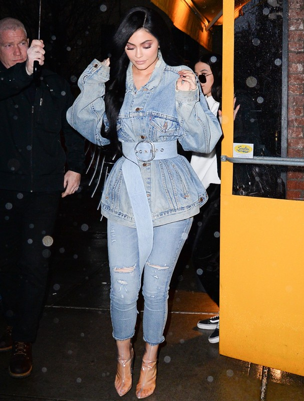 AK_677249 - New York, NY  - Kylie Jenner seen coming out of Sarafina Restaurant in Soho during a rain downpour with the help of an umbrella carrier.  She was seen in a denim jacket, denim capri jeans, and see-through boots as she tried to keep her balance (Foto: AKM-GSI)