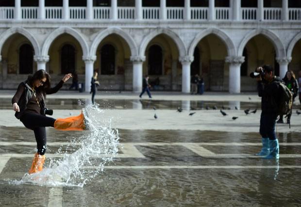 Casal em lua-de-mel tira foto em meio a enchente na Praça de São Marcos, em Veneza (Foto: Olivier Morin/AFP)