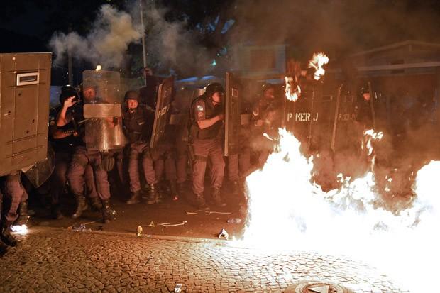 Manifestantes atiram bomba em direção aos policiais (Foto: Yasuyoshi Chiba/AFP)