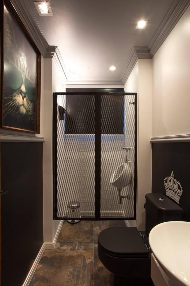 Lavabo | Há piso de porcelanato Ceusa e meias-paredes pretas na área que evoca um banheiro de pub. O mictório fica no antigo boxe com porta de chapa metálica perfurada (Foto: Lucas Cuervo Moura / Editora Globo)