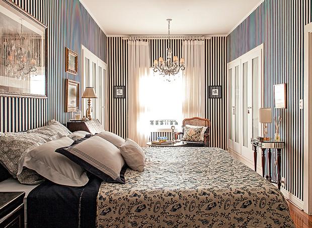 O arquiteto Rogério Ribas respeitou a linguagem da casa, dos anos 1940. Vetada a reforma, a solução para dar mais graça ao quarto foi revestir as paredes com lona listrada azul-marinho. A roupa de cama segue o tom, mas com estampa diferente (Foto: Victor Affaro/Casa e Jardim)