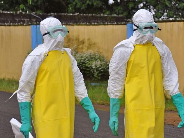 Médicos se preparam para retirar corpo de homem que suspostamente morreu vítima de ebola (Foto: AP)