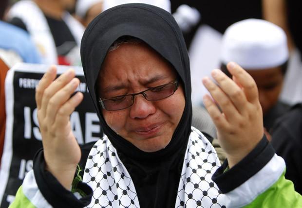 Muçulmana protesta contra as operações militares de Israel em Gaza nesta sexta-feira (16), em protesto diante da embaixada dos EUA em Kuala Lumpur, capital da Malásia (Foto: Lai Seng Sin/AP)