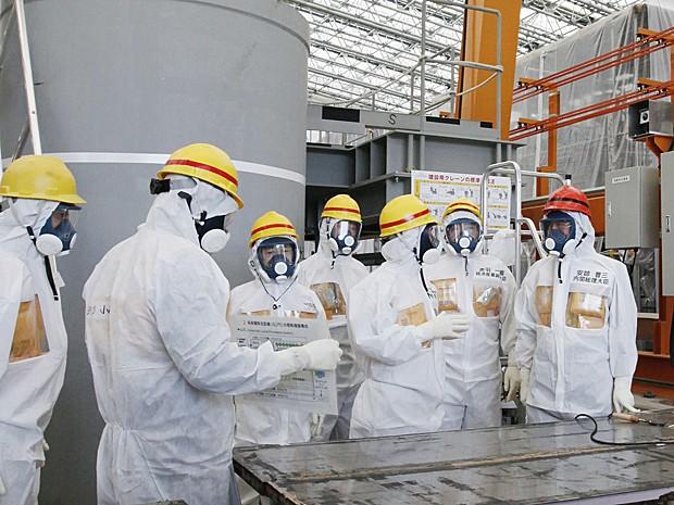 Primeiro-ministro japonês, Shinzo Abe (dir.) e chefe da planta de Fukushima, Akiro Ono (terceiro da dir. para esq.) fazem inspeção na usina nuclear nesta quinta (19) (Foto: Japan Pool/AP)