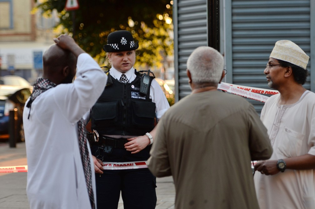 Policial conversa com moradores de Finsbury Park, no norte de Londres, após uma van avançar sobre muçulmanos na madrugada desta segunda-feira (19) (Foto: Victoria Jones/PA via AP)