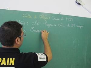 Professor escrevendo a matéria e a letra da música na lousa (Foto: Mariane Rossi/G1)