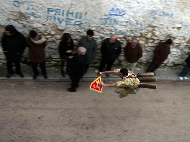 Participante do tradicional festival 'Endiablada' passa por pedestres saltando sem parar com sinos presos à cintura, em rua de Almonacid del Marquesado, na região central da Espanha. Fiéis costumam sair como demônios nas ruas para celebrar San Blas. (Foto: Sergio Perez/Reuters)