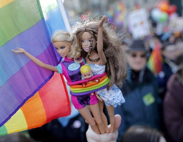 Manifestante segura bonecas Barbie em marcha pelas ruas de Paris pelo casamento gay (Foto: Reuters)