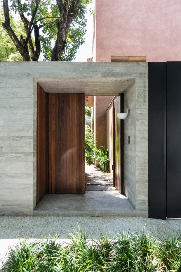Entrada social. Na lateral da garagem, uma pequena caixa de concreto protege o acesso principal, com portão de cumaru (Foto: Ruy Teixeira / Editora Globo)