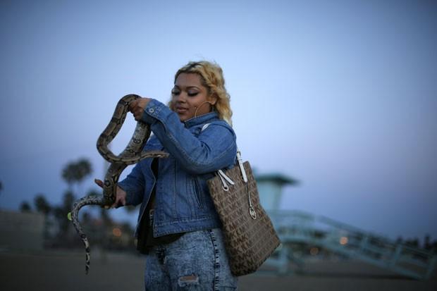 A adolescente Star Alvarez, de 19 anos, chamou atenção enquanto passeava com sua cobra de estimação em uma praia em Venice Beach, na região de Los Angeles, no estado da Califórnia (EUA) (Foto: Lucy Nicholson/Reuters)