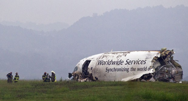 Bombeiros trabalham em frente à carcaça da parte frontal do avião acidentado no Alabama (Foto: Butch Dill/AP)