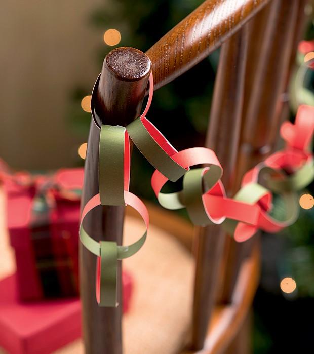 Aqui, o fio é uma corrente de elos que pode ser feita com pequenos retalhos de papel de maneira fácil e rápida. Pendure-a na parede, nas escadas ou, como mostra a foto, nas cadeiras. Que tal fazer de diferentes cores para marcar os assentos? (Foto: Iara Venanzi/Editora Globo)