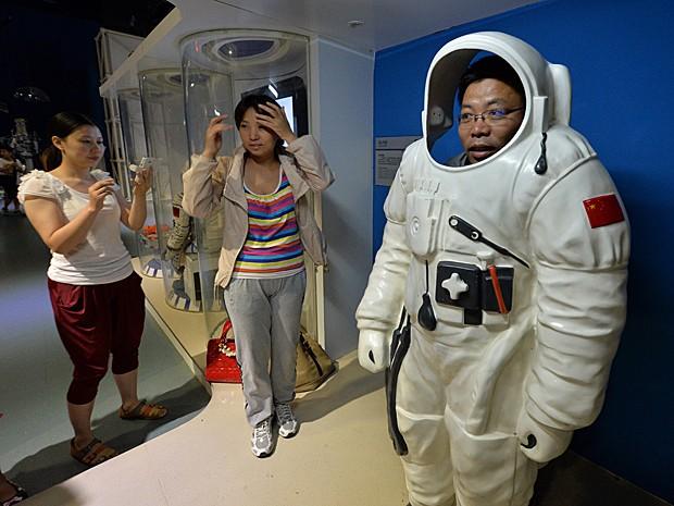 Homem veste roupa de astronauta no Museu de Ciência e Tecnologia de Pequim (Foto:  Mark Ralston/AFP)