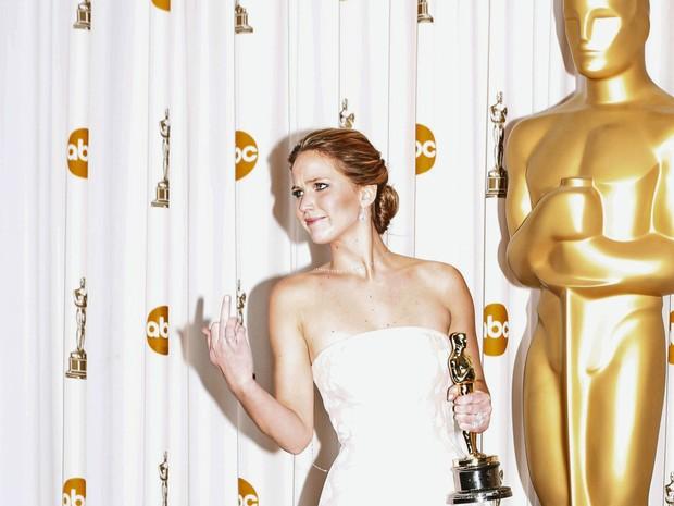 Após levar a estatueta de Melhor Atriz e tomar um tombo ao subir no palco, Jennifer Lawrence reage às piadas de fotógrafos alertando-a para ter atenção com os degraus quando ela foi posar para fotos no backstage (Foto: Mike Blake/Reuters)