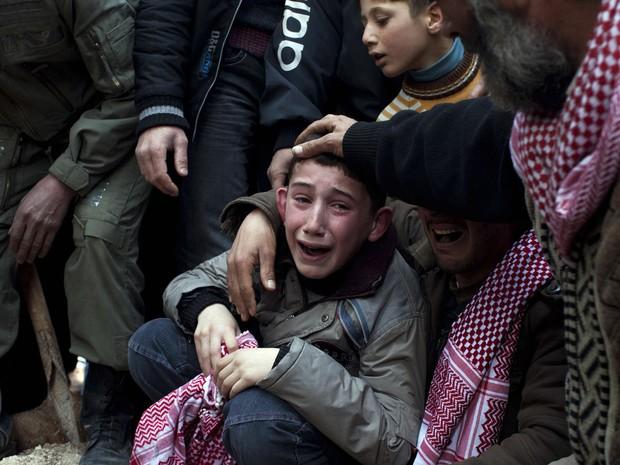 Ahmed chora a morte do pai Abdulaziz Abu Ahmed Khrer, que foi morto por um franco-atirador do Exército sírio em Idlib, ao norte da Síria. (Foto: Rodrigo Abd/AP)