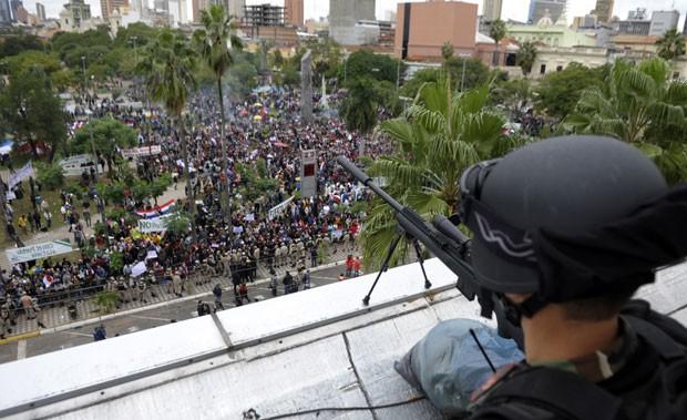Atirador do Exército observa nesta sexta-feira (22) multidão reunida em apoio ao presidente Fernando Lugo em frente ao prédio do Congresso do Paraguai, em Assunção (Foto: AFP)