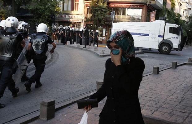Mulher cobre o rosto para se proteger do gás lacrimogêneo usado pela política turca para dispersar a aglomeração que protestava na Praça Taksim, em Istambul, neste sábado (6). (Foto: Thanassis Stavrakis/Associated Press)