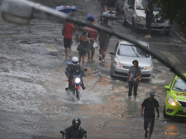 Pedestres tentam caminhar pelos poucos locais secos (Foto: Rodrigo Gorosito/ G1)
