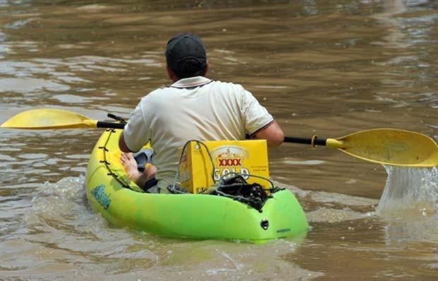 Em janeiro de 2011, um morador de Rockhampton, cidade afetada por inundações na Austrália, foi flagrado usando um caiaque para ir buscar cerveja (Foto: Torsten Blackwood/AFP)
