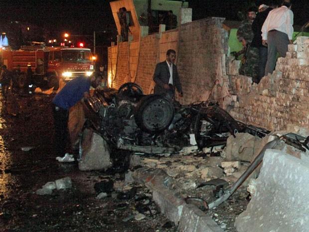 Pessoas se reúnem em torno de destroços após explosão de dois carros-bomba o centro da capital Síria neste domingo (13) (Foto: Ana Handout/ Reuters)