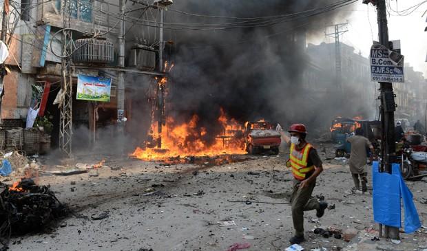 Homem corre perto de local onde houve explosão no Paquistão neste domingo (29). (Foto: Hasham Ahmed/AFP)