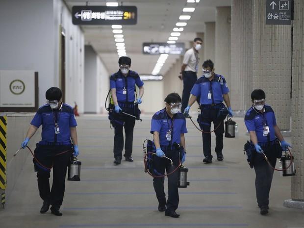 Empregados de uma companhia sanitária desinfetam chão do aeroporto internacional Gimpo, em Seul, nesta quarta-feira (17). A medida é para evitar a proliferação de casos de Mers (Foto: Kim Hong-Ju)