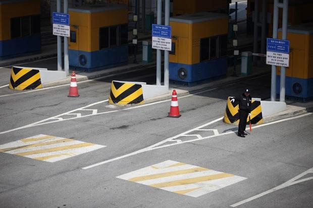 Soldado sul-coreano monta guarda nesta quinta-feira (4) em estrada que leva ao complexo de Kaesong (Foto: AFP)
