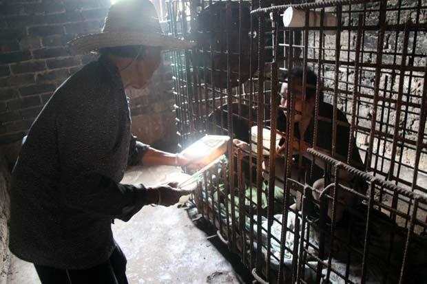 Enjaulado, Wu Yuanhong recebe comida de sua mãe na vila de Lijiachong, na China (Foto: AFP)