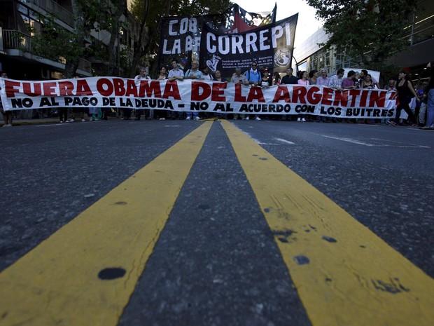 Manifestantes exibem um cartaz com a mensagem 'Obama, saia da Argentina - Não ao pagamento da dívida, não ao acordo com (credores) abutres' durante um protesto em Buenos Aires contra a visita do presidente americano Barack Obama à Argentina (Foto: Martin Acosta/Reuters)