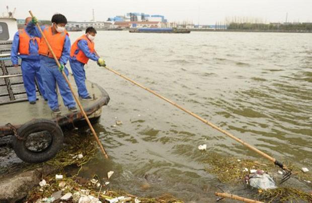 Na última semana, funcionários do governo da China retiram lixo que flutua na região de Xangai (Foto: Peter Parks/AFP)