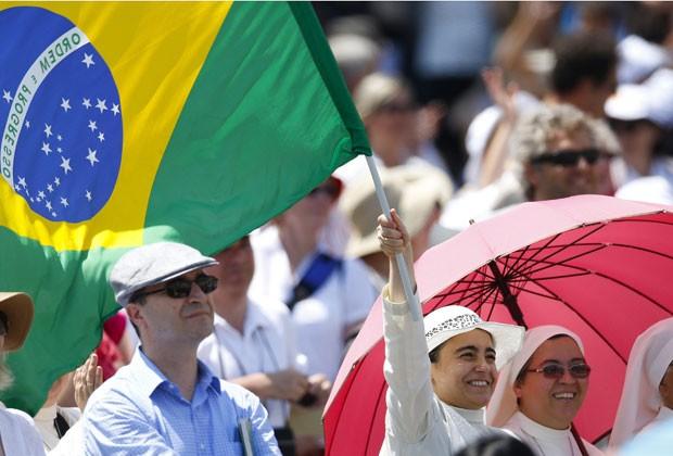 Freira com bandeira brasileira é vista na Praça São Pedro neste domingo (21) (Foto: Max Rossi/Reuters)