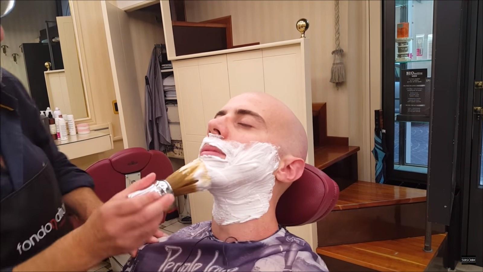 Uma cena habitual: Massimo sentado em uma cadeira sendo barbeado (Foto: Reprodução/Youtube)