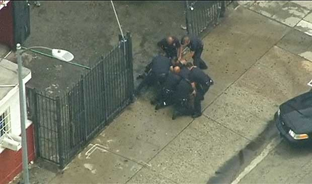 Rapaz escorrega e é preso por vários policiais. (Foto: BBC)