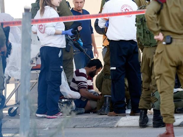 Médicos e forças de segurança israelenses cercam motorista palestino baleado depois de tentar jogar seu carro contra policiais israelenses no posto de controle de fronteira Qalandia, entre Jerusalem e Ramallah (Foto:  AFP PHOTO / ABBAS MOMANI)