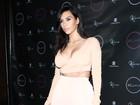 Kim Kardashian usa blusa decotada para badalar com as irmãs