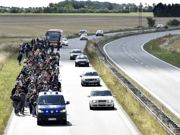 Grupo de imigrantes caminha em estrada da Dinamarca, ao norte da cidade de Rodby; eles devem prosseguir para a Suécia (Foto: AFP PHOTO / Scanpix Denmark / BAX LINDHARDT DENMARK OUT)