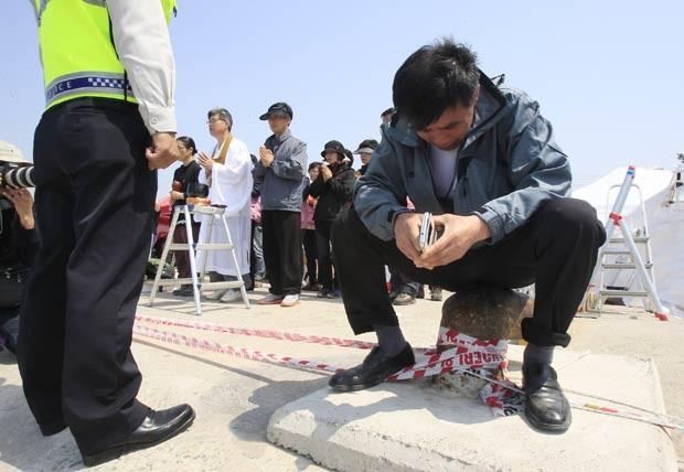 Parente de vítima do naufrágio chora no porto de Jindo enquanto aguarda operações de resgate (Foto: Ahn Young-joon/AP)