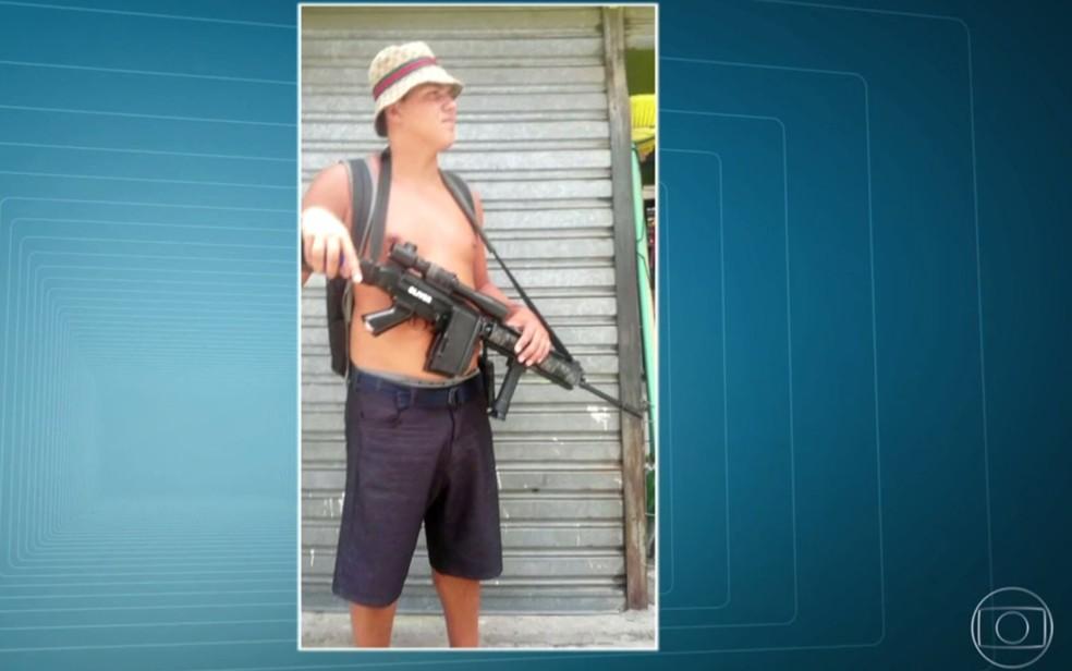 Homem aparece com arma de grande poder de fogo (Foto: Reprodução/TV Globo)