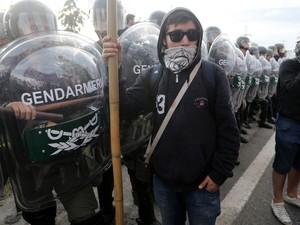 Grevista se posiciona em frente a policiais durante bloqueio a avenida em greve geral na Argentina (Foto: Enrique Marcarian/Reuters)
