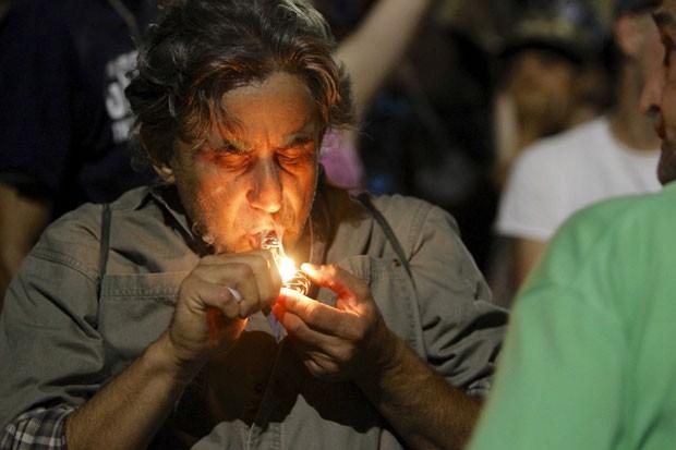 Homem acende cigarro de maconha durante celebração pela liberação do uso recreacional da droga em Portland, no Oregon, nos EUA, na noite desta quarta-feira (1º) (Foto: Steve Dipaola/Reuters)