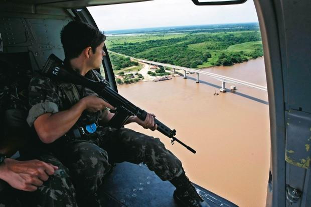 PORTA DE ENTRADA Soldado do Exército em patrulha sobre o Rio Paraguai, na fronteira com a Bolívia. Fronteiras são usadas para o tráfico de armas e drogas  (Foto: Joel Silva/Folha Imagem)